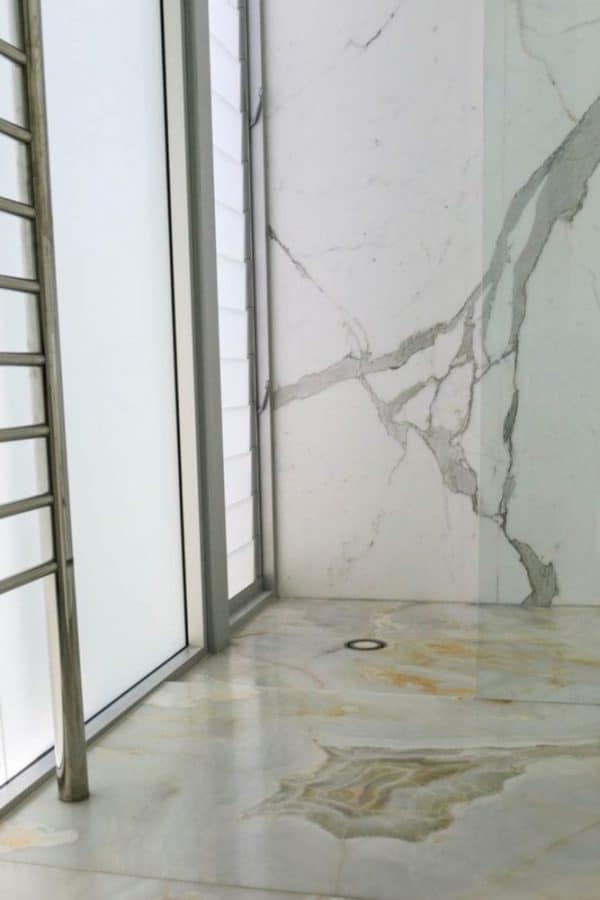 calacatta shower wall and white onyx floor